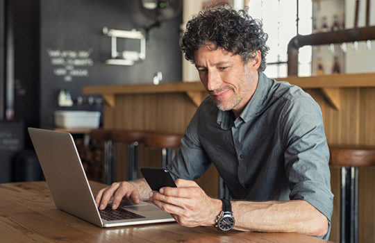Man sitting at table in front of laptop while using his phone in a cafe