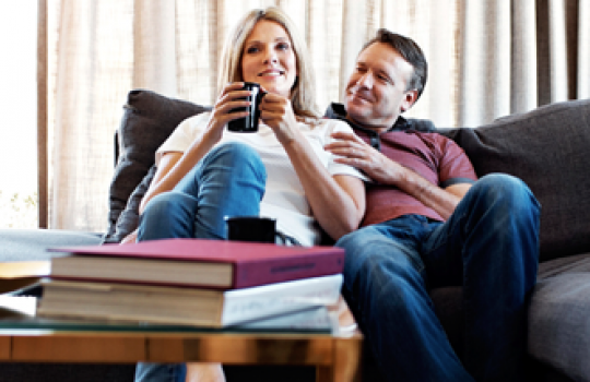 Fixed terms savings account, coffee table and books in front of a woman holding a black mug sitting with a man on a sofa