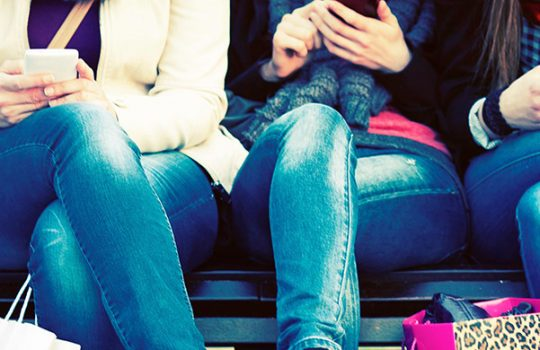 Ways to bank, social media, women's knees wearing blue jeans and holding smart phones in hands
