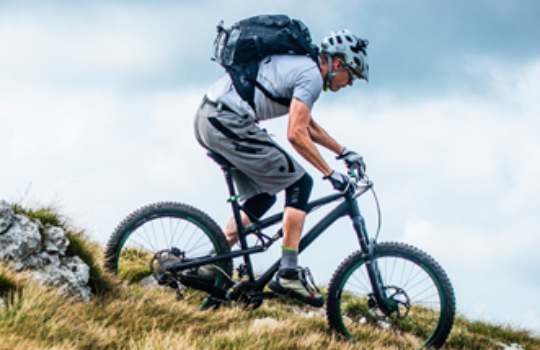 Online savings account, cyclist wearing helmet, gloves and backpack riding a mountain bike on a mountainous trail
