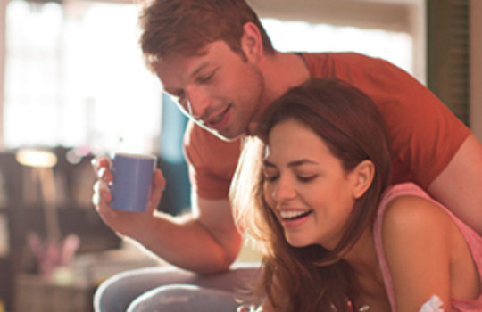 Insurance, home, woman smiling with a man holding a blue cup