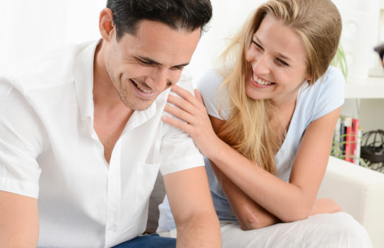 Insurance, income protection, woman smiling and touching a hand on shoulder of a man wearing a white short sleeved shirt