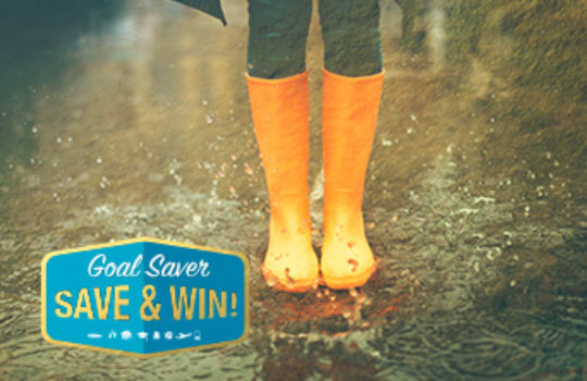 Savings goals guide, orange wellington boots splashing in rainy puddles, overlay text reads goal saver save and win