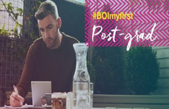 Life moments, graduate, my first postgrad, man sitting at outside table, overlay text reads hashtag boimyfirst post-grad