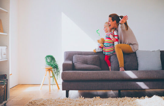 Life moments, buying your first home, woman holding child whilst sitting on the back of a living room sofa