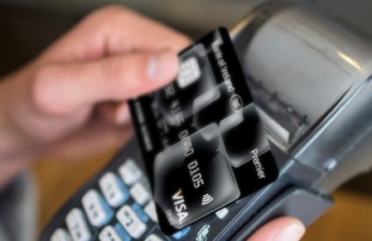 Premier, benefits, hand tapping Bank of Ireland Visa card on contactless credit card machine