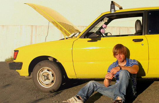 Life moments, buying a car, man wearing t-shirt and jeans sitting on the ground leaning against a yellow car with bonnet open