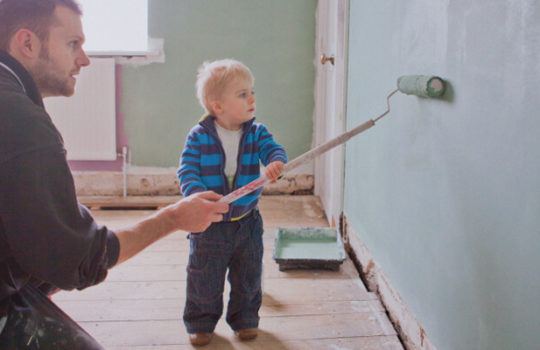 Life moments, doing up your home, toddler beside man kneeling on floor painting a wall with a paint roller
