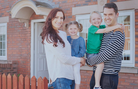Life moments, moving house, young couple holding son and daughter in their arms in front of a red brick house