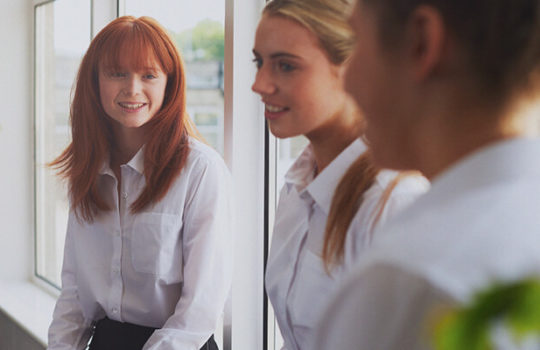 Life moments, starting secondary school, three female students wearing white shirts standing near a large indoor window