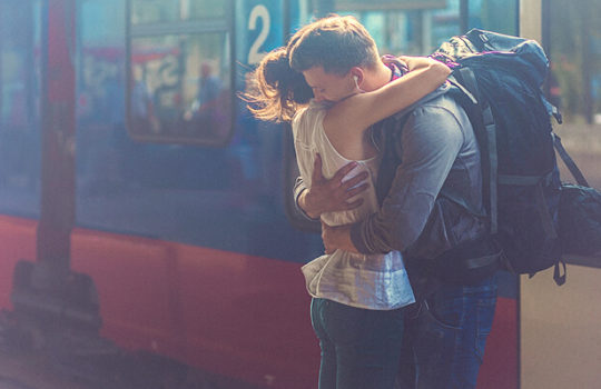 Life moments, travelling after college, man with a backpack hugging a woman beside a blue and red train