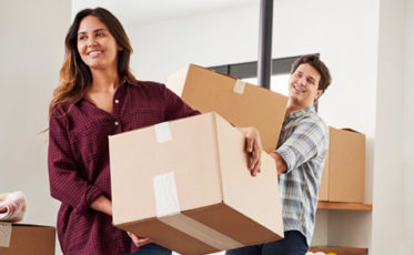 Couple moving boxes into first home