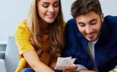 Couple on couch looking at shopping receipts