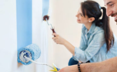 Couple painting interior wall with rollers