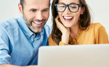 Couple reading property search tips on a laptop