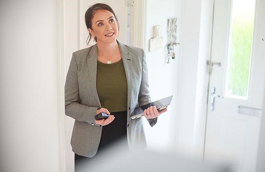 Woman buy to let investor with phone near door