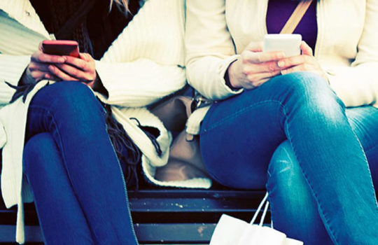 Two girls in jeans with their legs crossed sitting on a bench using their phones