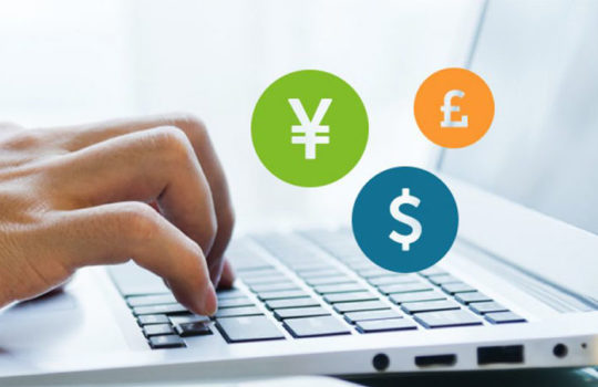 A hand typing on a laptop with the Japanese Yen, US Dollar and British Sterling symbols