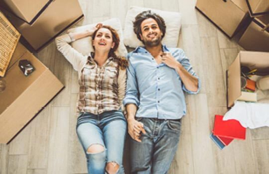 Couple lying on floor near space saving boxes