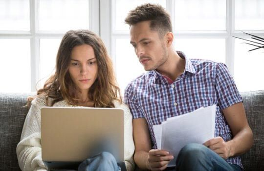 Couple looking at laptop to switch mortgage